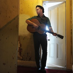 Edinburgh singer songwriter Dean Owens with guitar in yellow close